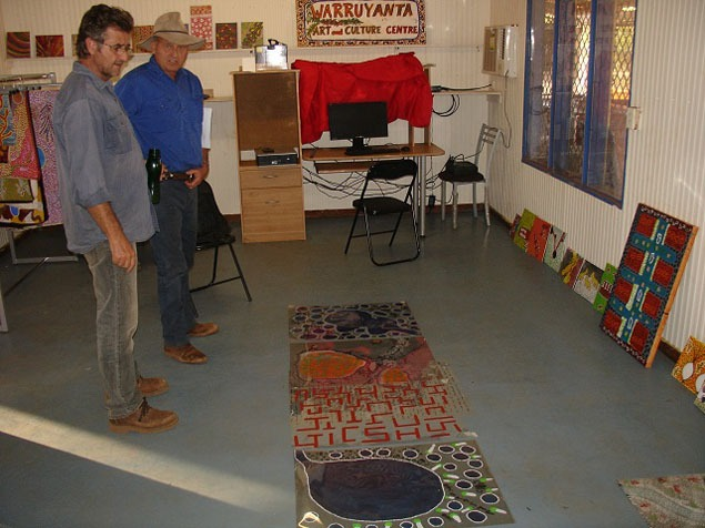 Printmaker Basil Hall and conservationist Guy Fitzhardinge with the acetates on the floor of the Warruyarnta Art Centre in Mulan. Photo by John Carty.