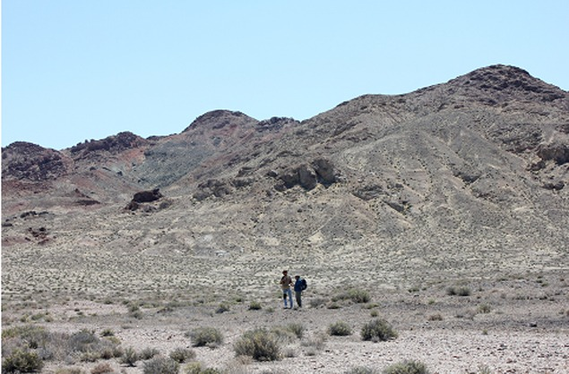 Bill Fox standing with Steve Glotfelty at the foot of the Mopong Hills. Note the light horizontal lines on the hills below the outcroppings, which are ancient lakeshore strandlines. Humboldt Cave is located above the old beaches and out of sight.