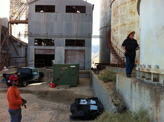 Matt Coolidge peers at the three-inch lens mounted into the side of the silo camera. The green box in the background is the portable U.S. Army darkroom. The washing trays are in the foreground. Photo by Bill Fox, 2012.