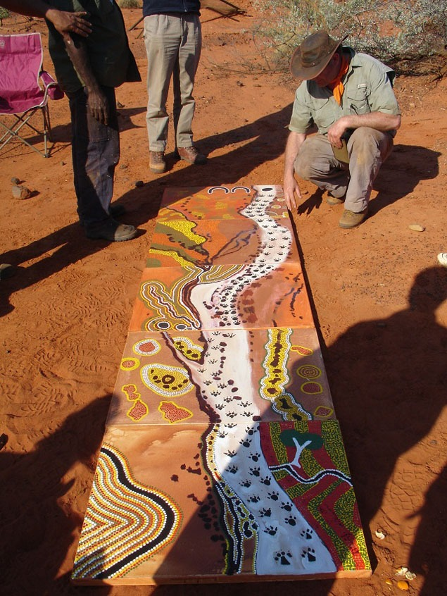Chris Curran examining the Parnkupirti Creek painting at the end of the first day's work. Photo by John Carty.