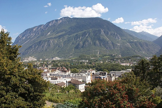 View from our window of Sierre. Vineyards, and gardens, traditional architecture and construction cranes, and across the valley the straight vertical line of a hydroelectric pipeline. Photo by Sara Frantz.