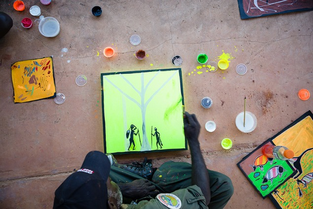 Djelk Ranger and artist Greg Wilson making a start on a fluorescent paint canvas. Photo by Hugo Sharp.